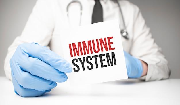 Adesivo bianco con testo sistema immunitario nelle mani del medico con uno stetoscopio
