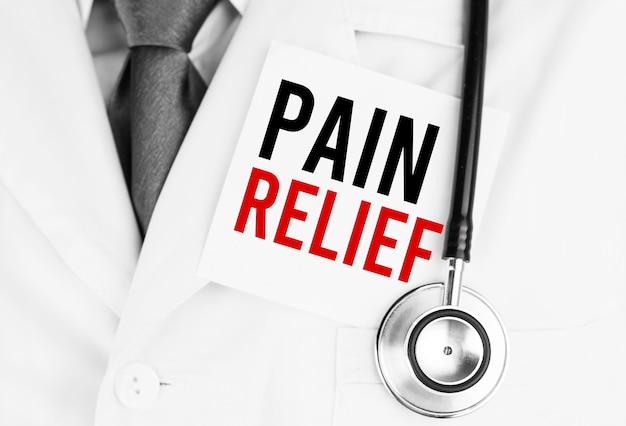 Adesivo bianco con testo pain relief sdraiato sulla veste medica con uno stetoscopio