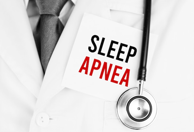 Adesivo bianco con testo apnea del sonno sdraiato sulla veste medica con uno stetoscopio