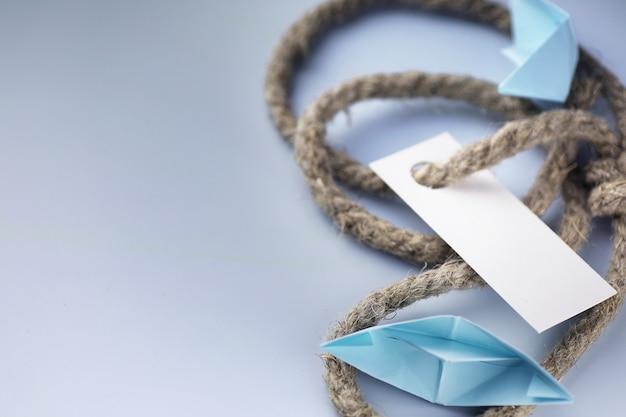 Adesivo bianco con corda intrecciata spessa e origami di carta nave