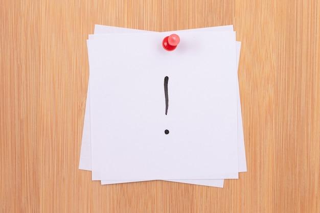 Note adesive bianche con punto esclamativo appuntate alla bacheca in legno