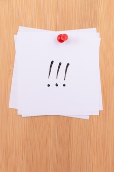Note adesive bianche con tre punti esclamativi appuntate alla bacheca in legno
