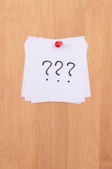 Note adesive bianche con tre punti interrogativi appuntati alla bacheca di legno