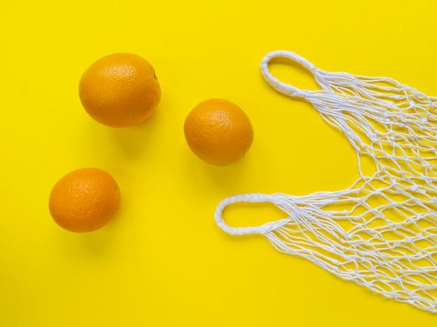Eco bag in filo di cotone bianco e tre arance su sfondo giallo. piatto semplice. ecologia concetto di rifiuti zero.