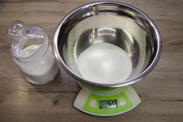 Zucchero bianco in una ciotola sulla bilancia