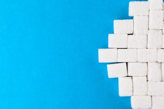 Cubi dello zucchero bianco su una priorità bassa blu luminosa