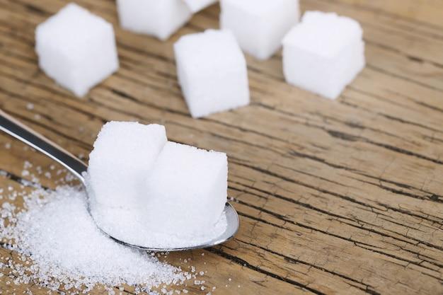 Zucchero bianco in cucchiaio di legno sulla tavola di legno