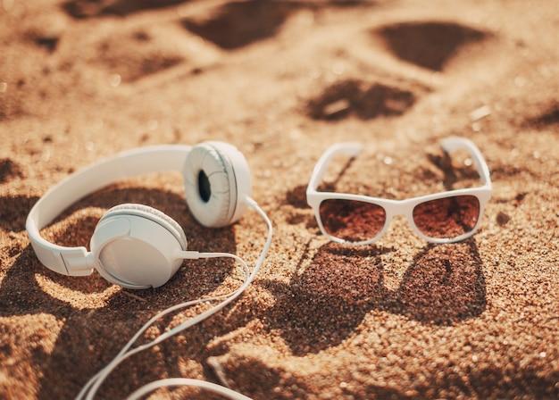 Occhiali da sole bianchi e cuffie sulla sabbia