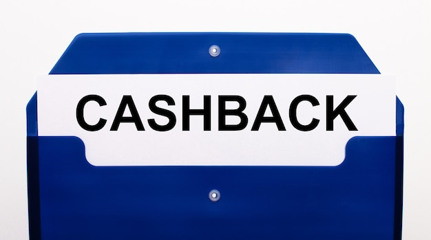 Su una superficie bianca, una cartella blu per i documenti. nella cartella c'è un foglio di carta con la parola cashback.