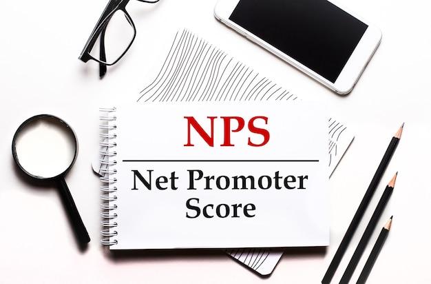 Su una superficie bianca occhiali, una lente d'ingrandimento, matite, uno smartphone e un taccuino con il testo nps net promoter score