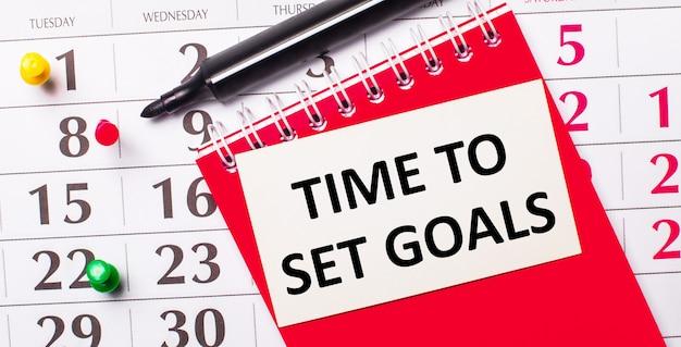 Su una superficie bianca si trova un taccuino con le parole time to set goals, occhiali, una lente d'ingrandimento, pennarelli verdi e una pianta verde