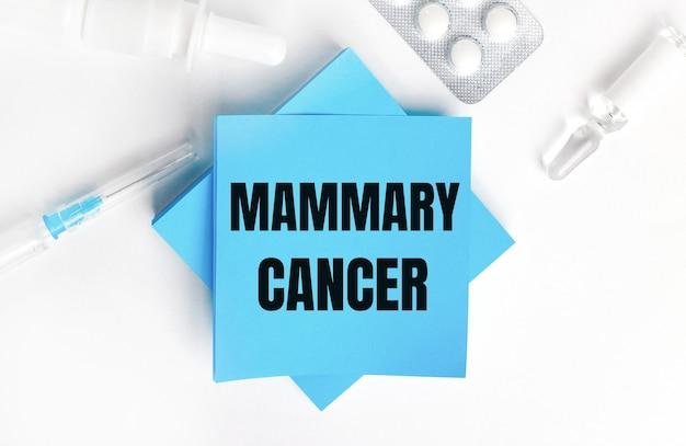 Su una superficie bianca, una siringa, una fiala, pillole, una fiala di medicinale e adesivi azzurri con la scritta mammary cancer