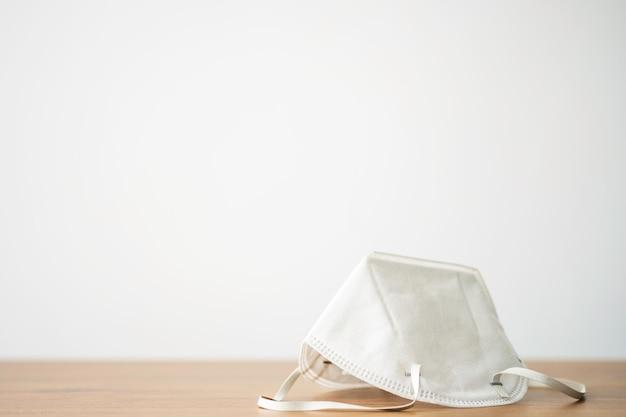 Maschera chirurgica bianca su tavola di legno da indossare per proteggersi da covid-19 o virus corona, polvere da inquinamento, batteri. concetto sanitario e chirurgico.