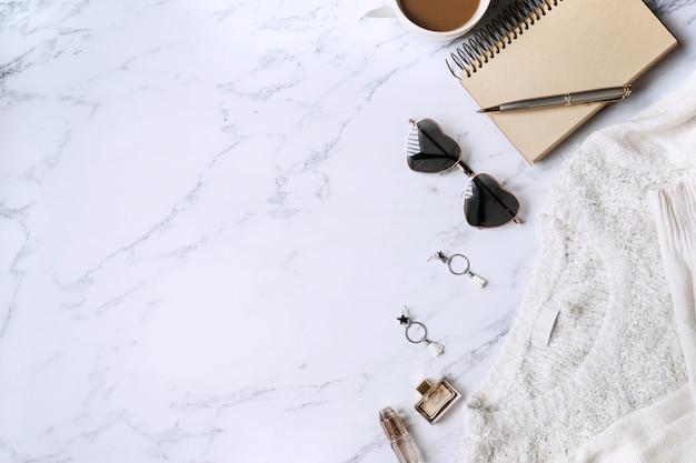 Maglione bianco, accessori da donna, caffè, taccuino, smart phone sulla vista superiore del fondo di marmo