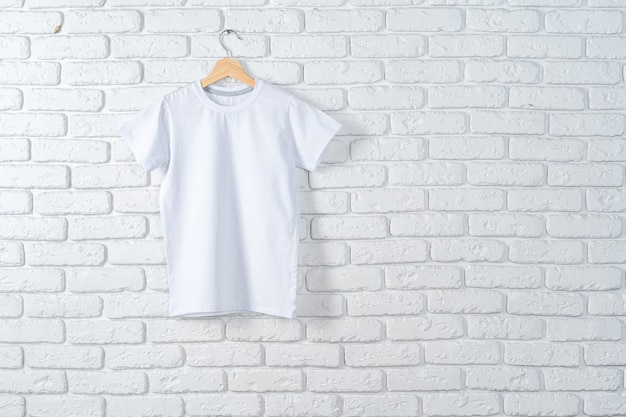 Maglietta bianca che appende sul gancio contro il muro di mattoni, spazio della copia