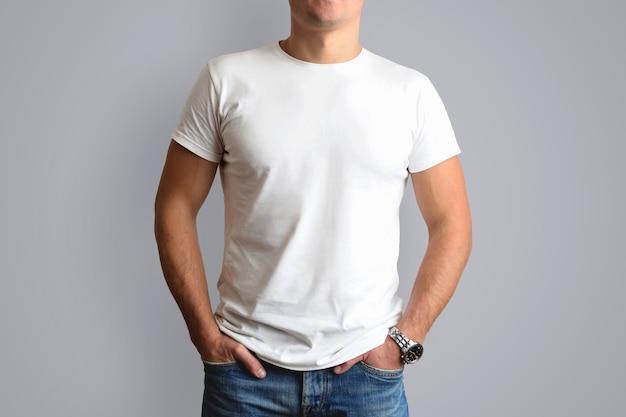 Maglietta bianca su una giovane muffa in blue jeans. isolato su un muro grigio.