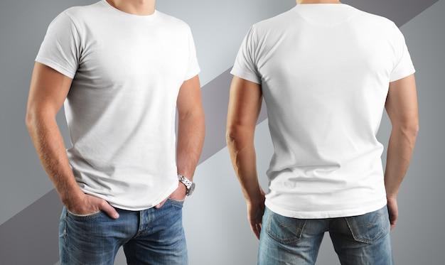 Magliette bianche sull'uomo, posa davanti e dietro isolato su un muro grigio con una striscia diagonale
