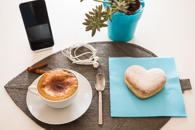 Tavolo bianco preparato per una colazione felice con un cappuccino caldo fatto in casa e una ciambella a forma di cuore. un cellulare e una pianta sul tavolo bianco