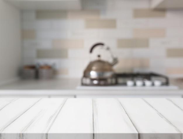 Superficie del tavolo bianco davanti al bancone della cucina a sfocatura