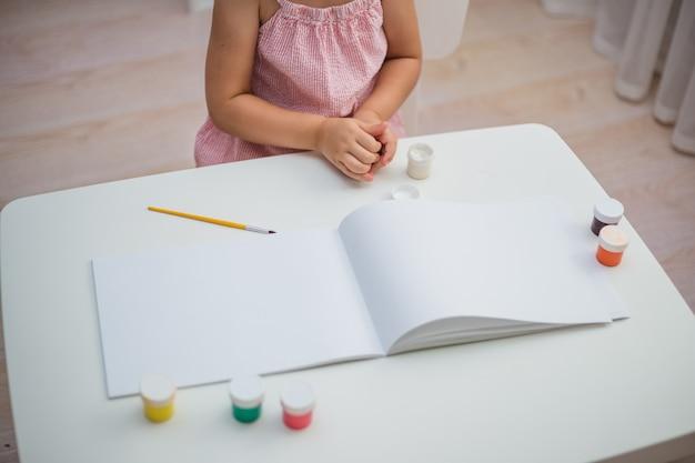 Tavolo bianco con accessori per album da disegno, pennelli, pittura