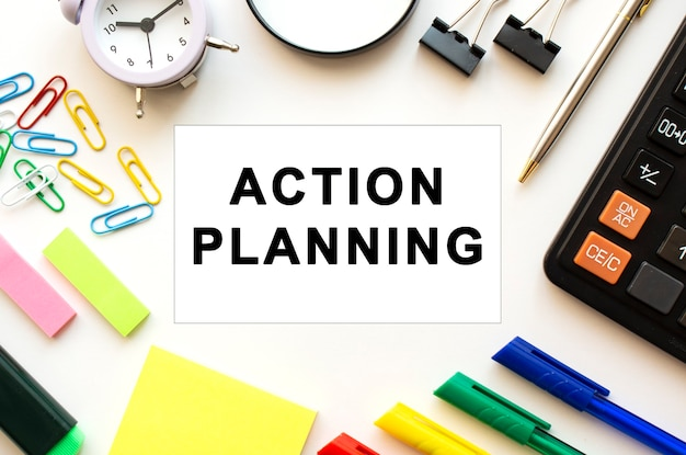 Tavolo bianco con penne colorate e altri articoli di cancelleria. testo sulla scheda action planning