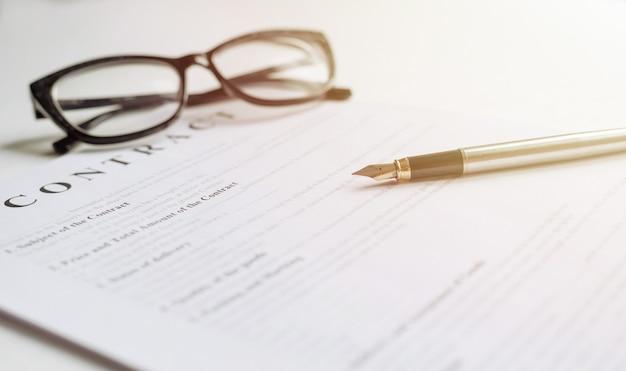 Tavolo bianco con carta contratto, bicchieri e penna a inchiostro