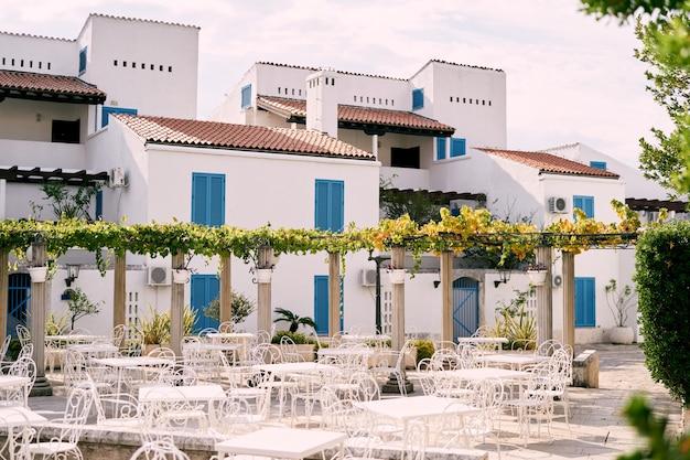 Tavoli e sedie bianchi sullo sfondo di un edificio residenziale
