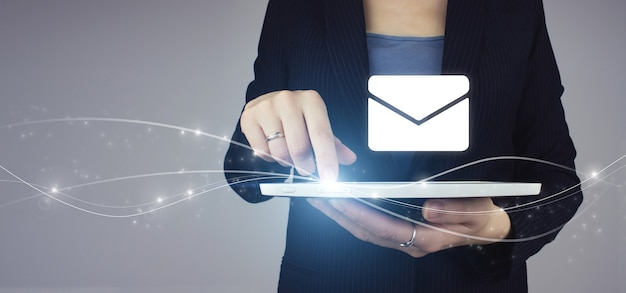 Compressa bianca in mano di donna d'affari con ologramma digitale segno di posta elettronica su sfondo grigio. invio newsletter