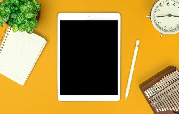 Tablet bianco con schermo mockup nero, sfondo minimalista della scrivania dell'ufficio, modello business e freelance con copia spazio foto
