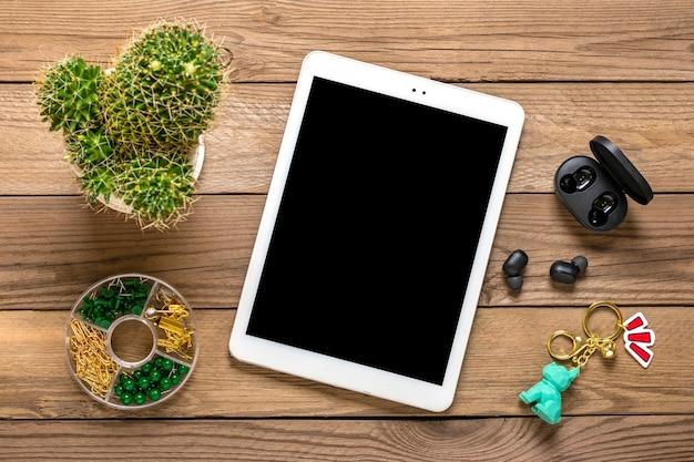 Tablet bianco con display a schermo nero e cuffie wireless, cactus su fondo in legno