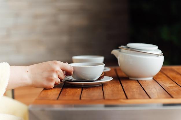 Stoviglie bianche, bollitore grande, tazza, ciotola, cucchiaio di porcellana su uno sfondo sfumato grigio
