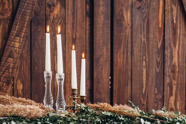Candele alte bianche in candelieri a cristallo su fondo strutturato di legno rustico.