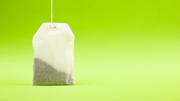 Bustine di tè bianche su uno spazio verde chiaro copia spazio.