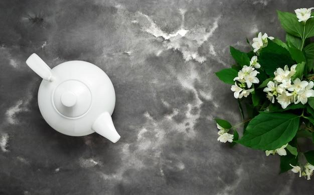 Teiera bianca, tisana, fiore di gelsomino, fondo piatto in marmo bianco nero. insegna di web lungo del modello di vista superiore del tè