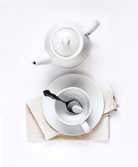Teiera bianca e tazza da tè vuota con cucchiaio isolato su sfondo bianco vista dall'alto piatta