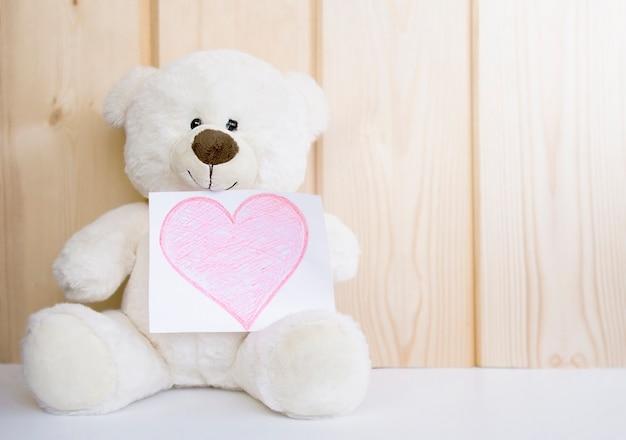 Orsacchiotto bianco con cuore disegnato su fondo di legno