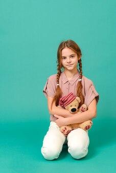 Adolescente bianco in pantaloni bianchi e una camicia rosa si siede con un orso giocattolo su una superficie verde