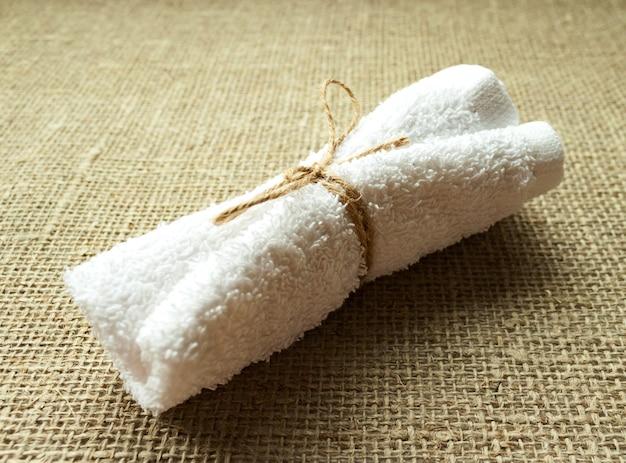 Asciugamano in spugna di cotone bianco arrotolato su sacco di tela di lino. spa, sauna, concetto di stile di vita sano. avvicinamento. messa a fuoco morbida selettiva. . copia del testo spazio.