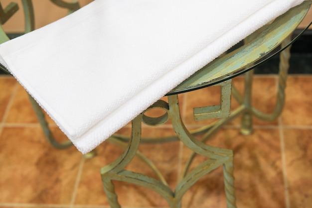 Asciugamano di spugna bianco su un tavolo di metallo nel bagno dell'hotel