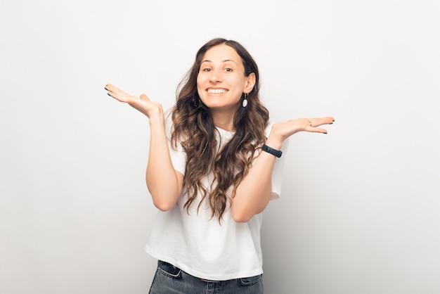 Foto a tema bianco di una giovane donna che alza le spalle o fa il gesto di sorpresa con le braccia.