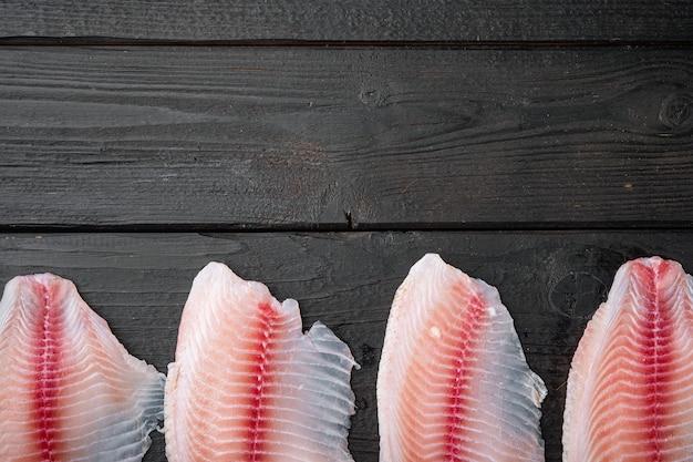 Tagli di filetto di pesce di tilapia bianca sul tavolo di legno nero