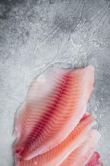 Tagli di filetto di pesce tilapia bianca su grigio