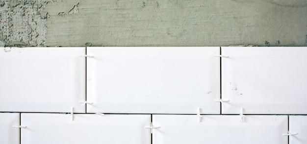 Piastrelle bianche posate sul cemento grigio. ristrutturazione lavori di riparazione di manutenzione nell'appartamento. restauro al chiuso. lavori in corso.
