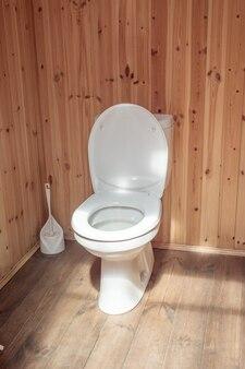 Toilette bianca con coperchio in plastica nella toilette esterna in legno spazzola in plastica sullo sfondo