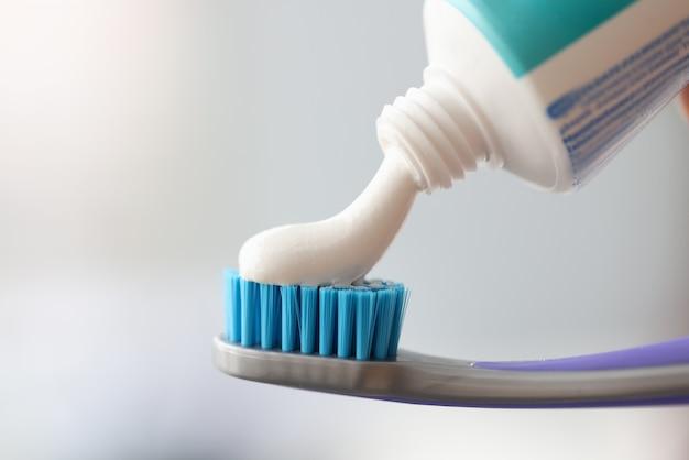 Il dentifricio bianco viene applicato allo spazzolino da denti. concetto di cura orale