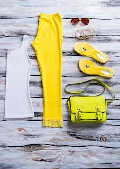 Top bianco e infradito. pantaloni gialli con borsa lime. abbigliamento estivo sullo scaffale bianco. abbigliamento colorato per donna.