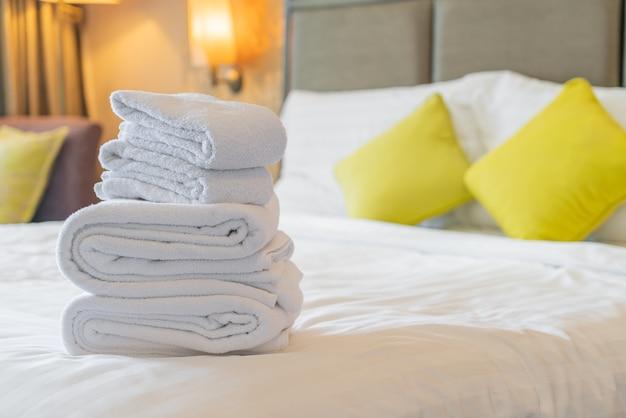 Asciugamano bianco piega sul letto in hotel resort