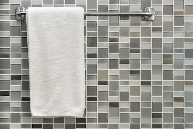 Asciugamano bianco su una gruccia sopra il fondo del muro di piastrelle in bagno