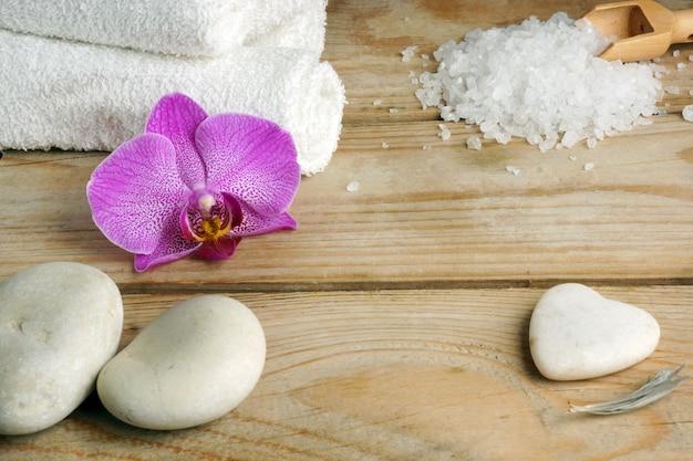 Asciugamani bianchi, sali da bagno e pietre per un massaggio caldo su un tavolo di legno