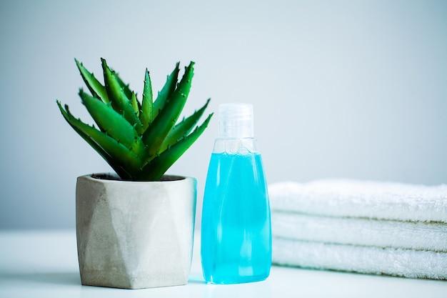 Asciugamani bianchi e gel doccia sul tavolo bianco con lo spazio della copia sul fondo della stanza da bagno.